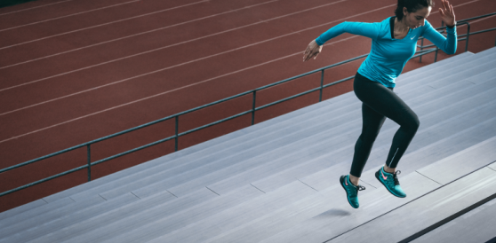 A woman wearing active gear runs up the stairs of an athletics stadium.