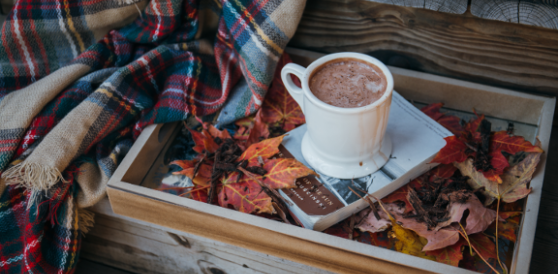 A mug of hot chocolate by a blanket and a book